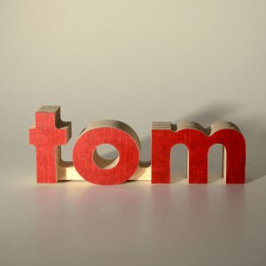 The name Tom routed out of red coated multiplex